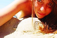 Green eyed beauty naked on the beach