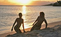 Two cool babes strip on the beach
